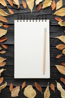 Vue de dessus du cahier avec des feuilles d'automne