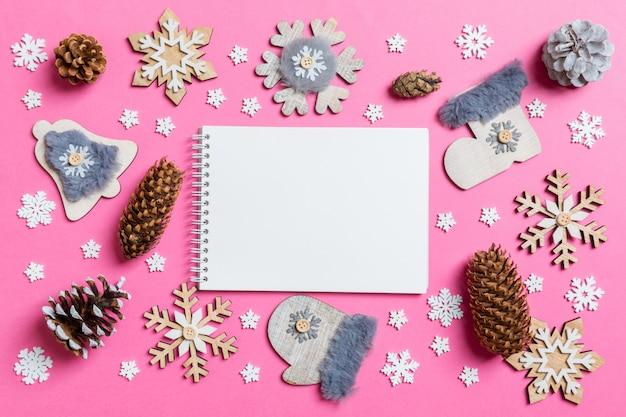 Vue de dessus du cahier, des jouets de vacances et des décorations rose noël