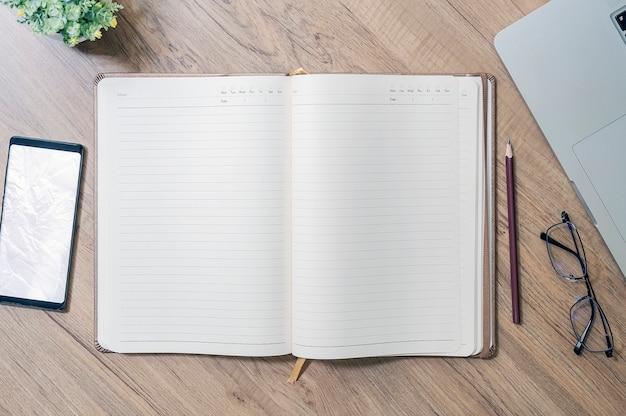 Vue de dessus du cahier ouvert page blanche avec des fournitures sur la table en bois.