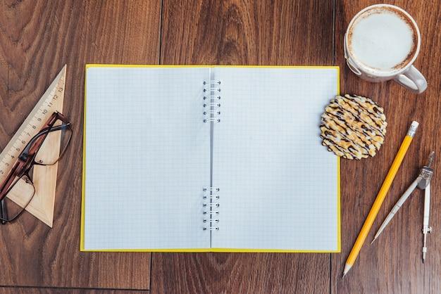 Vue de dessus du cahier, de la papeterie, des outils de dessin et de quelques tasses de café.