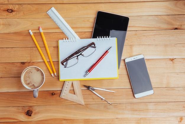 Vue de dessus du cahier, de la papeterie, des outils de dessin et de quelques verres. improviser.