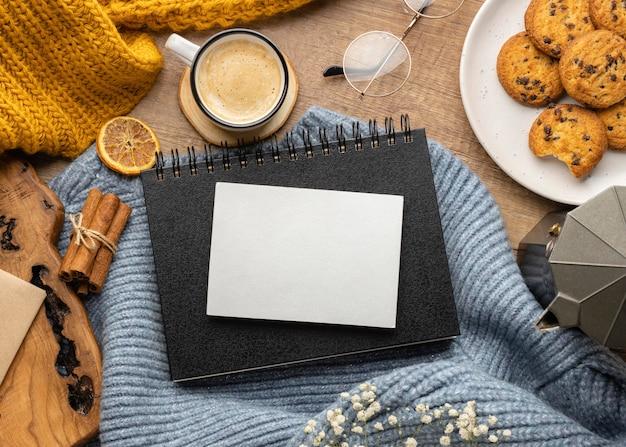 Vue de dessus du cahier sur le pull avec des biscuits et une tasse de café
