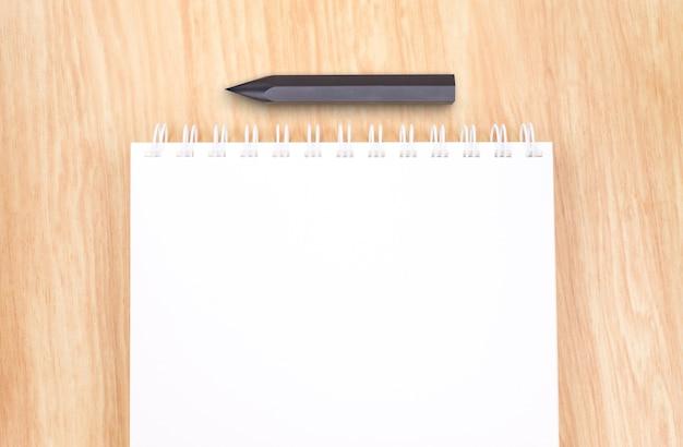 Vue de dessus du cahier de reliure à anneaux ouverts blanc avec un crayon noir sur la table en bois