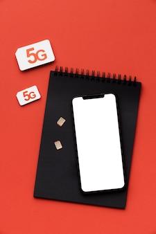 Vue de dessus du cahier avec smartphone et carte sim