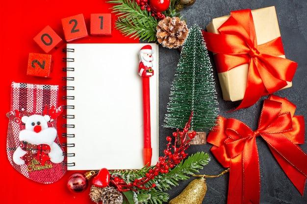 Vue de dessus du cahier à spirale accessoires de décoration branches de sapin numéros de chaussette de noël sur une serviette rouge et arbre de noël cadeau sur fond sombre