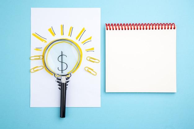 Vue de dessus du cahier à spirale lupa sur papier avec photo d'ampoule d'idée d'entreprise sur fond bleu