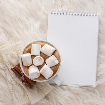 Vue de dessus du cahier avec tasse de chocolat chaud avec des guimauves