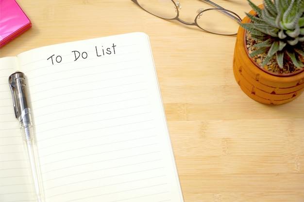 Vue de dessus du cahier vide avec la liste des tâches à faire sur l'espace de travail au bureau. copiez l'espace.