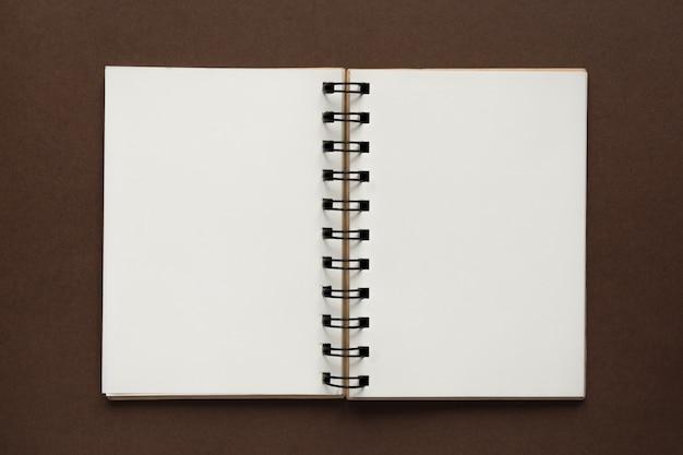 Vue de dessus du cahier vide ouvert avec couverture en papier recyclé sur fond coloré marron