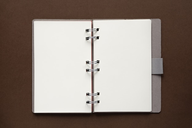 Vue de dessus du cahier vide ouvert avec couverture en papier recyclé sur fond marron