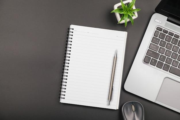 Vue de dessus du cahier vide vide avec ordinateur portable sur tableau noir