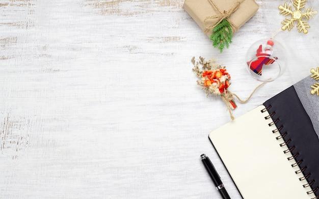 Vue de dessus du cahier vierge sur bois blanc avec des ornements de noël