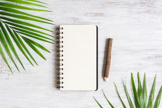 Vue de dessus du cahier vierge avec une feuille de palmier et un crayon en bois