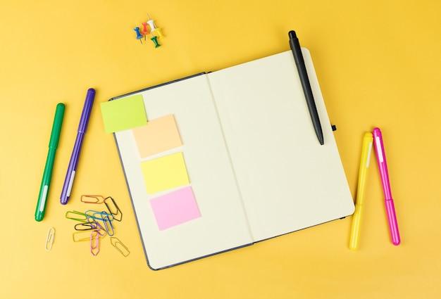Vue de dessus du cahier vierge et des fournitures scolaires comme des marqueurs colorés, des autocollants et des pinces sur fond jaune, un espace pour le texte.