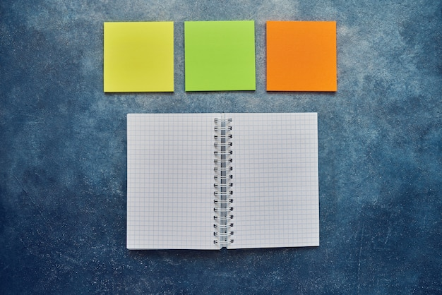 Vue de dessus du cahier vierge à spirale ouverte et autocollant vide note sur un fond bleu. retour au concept d'école. lay à plat, espace de copie