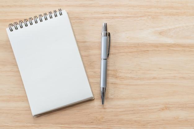 Vue de dessus du cahier vierge avec stylo et lumière naturelle sur table en bois.
