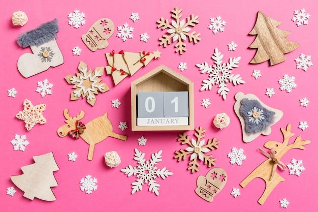 Vue de dessus du calendrier sur rose faite de décorations de vacances et de jouets.