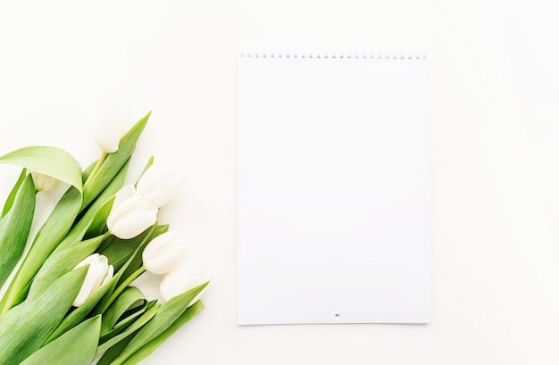 Vue de dessus du calendrier vierge pour la conception de maquettes et tulipes blanches. concept de printemps.