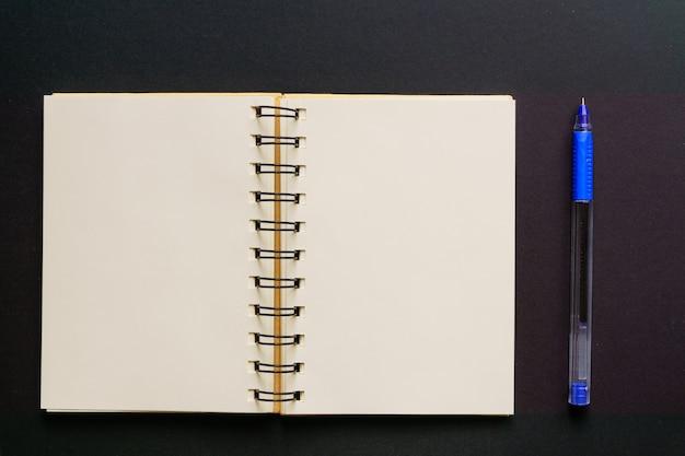 Vue de dessus du carnet kraft vide et stylo à bille bleu sur fond noir