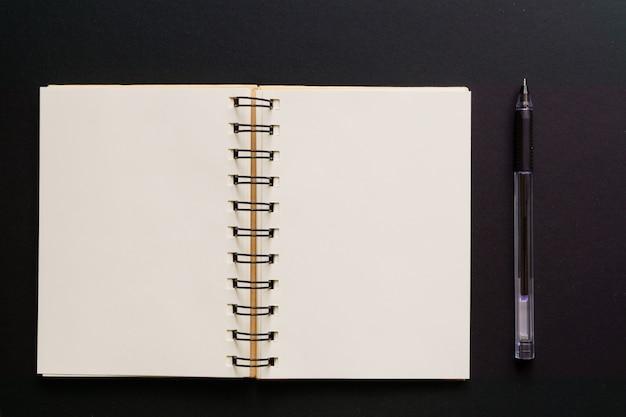 Vue de dessus du carnet kraft vide et stylo à bille sur fond noir