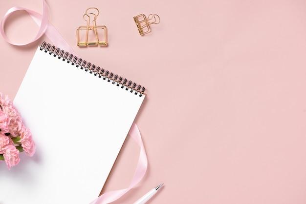 Vue de dessus du carnet de notes et des fleurs sur le bureau. pour le concept de planificateur de mariage