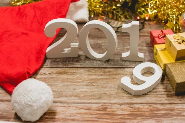 Vue de dessus du chapeau de noël, nombre 2019 et coffrets cadeaux sur fond en bois.