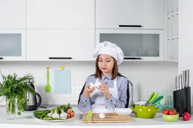 Vue de dessus du chef concentré et des légumes frais avec du matériel de cuisine et tenant des œufs dans la cuisine blanche
