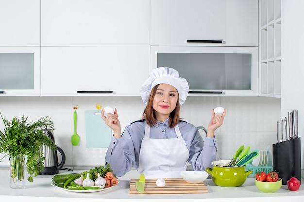Vue de dessus du chef et des légumes frais avec du matériel de cuisine et tenant des œufs dans la cuisine blanche