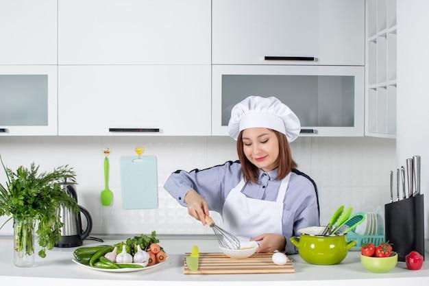 Vue de dessus du chef souriant et des légumes frais avec du matériel de cuisson et mélangeant l'œuf dans un bol blanc dans la cuisine blanche