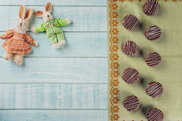 Vue de dessus du chocolat au miel fait maison brésilien recouvert de chocolat sur fond de bois avec des lapins en peluche et copie espace - pao de mel