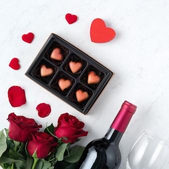 Vue de dessus du chocolat de la saint-valentin avec rose et vin, concept de conception de cadeau festif pour des rencontres de vacances spéciales.