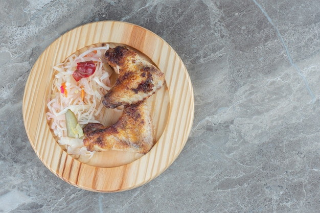 Vue de dessus du chou fermenté sur plaque de bois. avec poulet grillé.