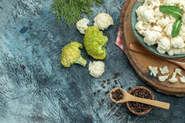 Vue de dessus du chou-fleur frais avec des cuillères et du poivre sur la table gris clair