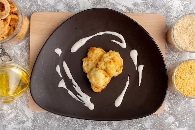 Vue de dessus du chou-fleur tranché cuit avec de l'huile et des haricots sur la surface blanc clair