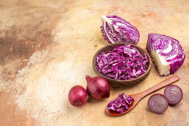 Vue de dessus du chou rouge haché dans un bol en bois et plusieurs oignons sont prêts pour la salade de betteraves sur un fond en bois avec un espace pour le texte