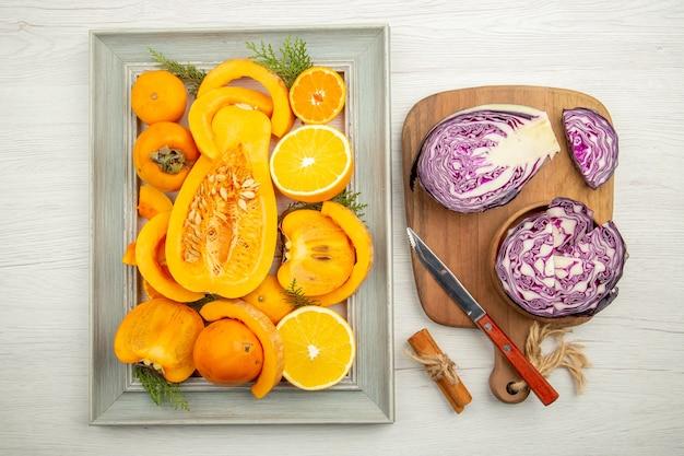 Vue de dessus du chou rouge haché dans un bol couteau sur une planche à découper courge coupée à la cannelle kaki oranges coupées sur cadre sur fond gris