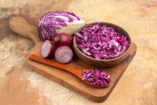 Vue de dessus du chou rouge haché dans un bol et quelques oignons sur une planche à découper en bois pour la préparation d'une salade maison sur un fond en bois avec espace de copie