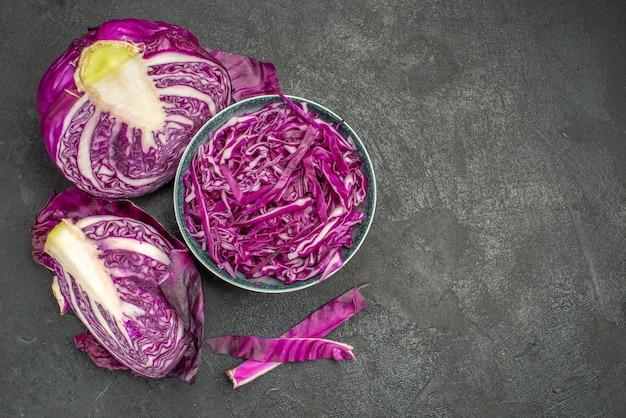 Vue de dessus du chou rouge en tranches de légumes frais sur fond sombre