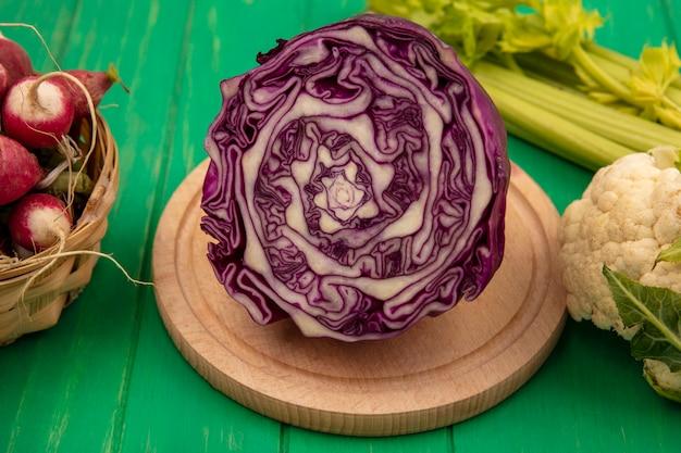 Vue de dessus du chou violet frais sur une planche de cuisine en bois avec des radis sur un seau avec chou-fleur et céleri isolé sur un mur en bois vert