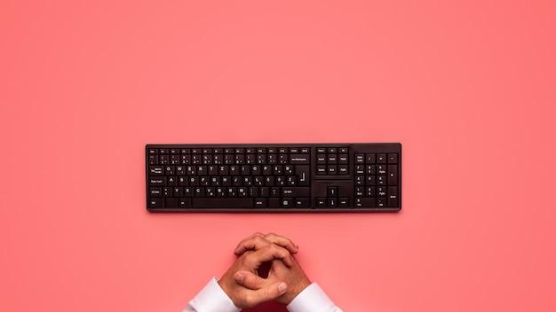 Vue de dessus du clavier d'ordinateur noir avec des mains masculines devant lui. sur fond rose.