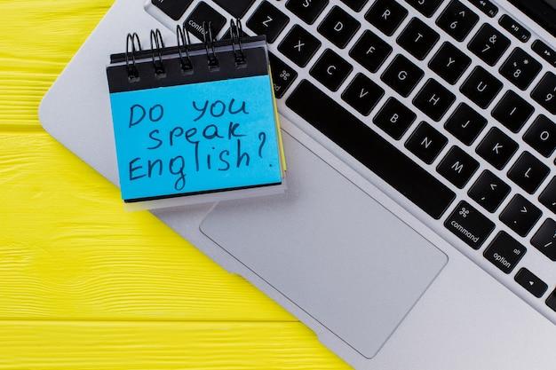 Vue de dessus du clavier d'ordinateur portable et des autocollants en papier. parles-tu anglais. fond en bois jaune.