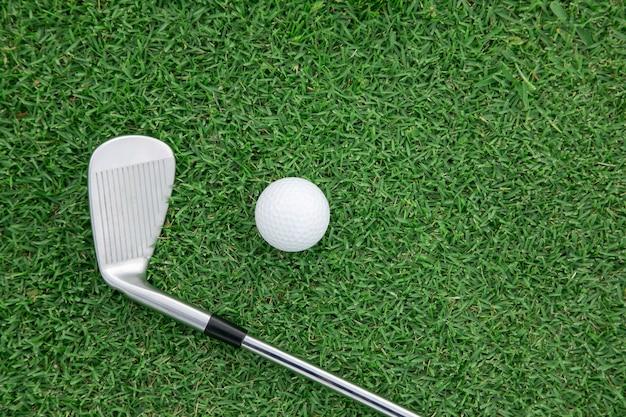 Vue de dessus du club de golf de fer et de la balle de golf sur l'herbe verte