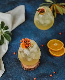 Vue de dessus du cocktail d'automne avec l'argousier et le jus d'orange dans un verre sur le mur bleu