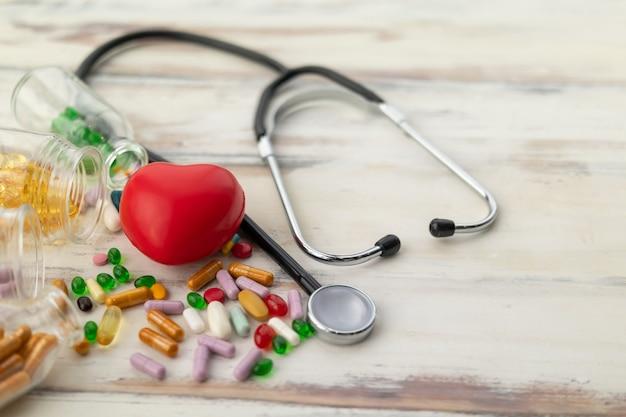 La vue de dessus du coeur rouge entouré de médicaments et de vitamines et le stéthoscope sur un plancher en bois crémeux
