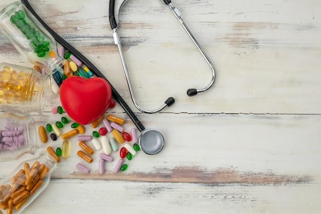 Vue de dessus du coeur rouge et de la médecine sur le plancher en bois