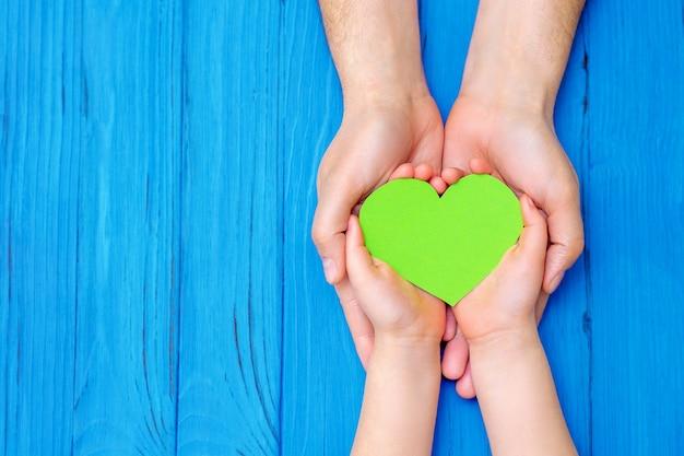 Vue de dessus du coeur vert dans les mains de l'adulte et de l'enfant sur fond bleu en bois. concept de la journée mondiale de l'environnement, de la journée mondiale de la santé et de la journée de la terre. espace de copie.