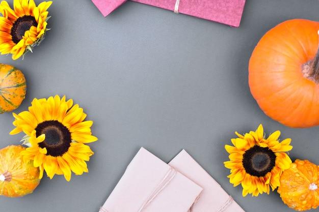 Vue de dessus du coffret cadeau artisanal, fleurs jaunes et citrouilles sur fond gris. carte de voeux vierge pour la conception de travaux créatifs. mise à plat