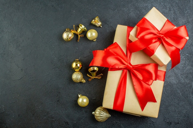 Vue de dessus du coffret cadeau avec ruban rouge et accessoires de décoration sur fond sombre