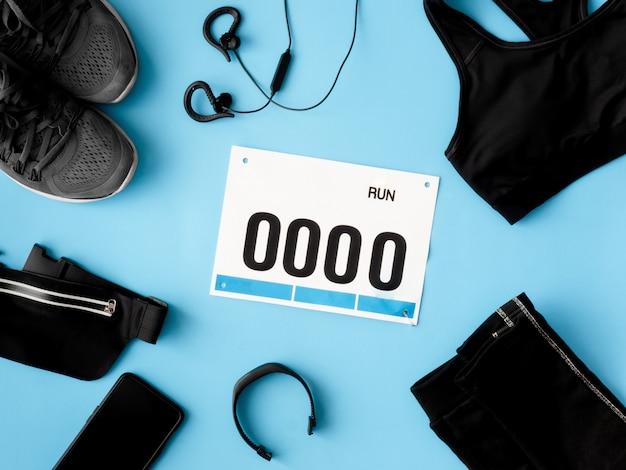 Vue de dessus du concept de course à pied avec chaussures de course, numéro de dossard et accessoires de course sur fond bleu.