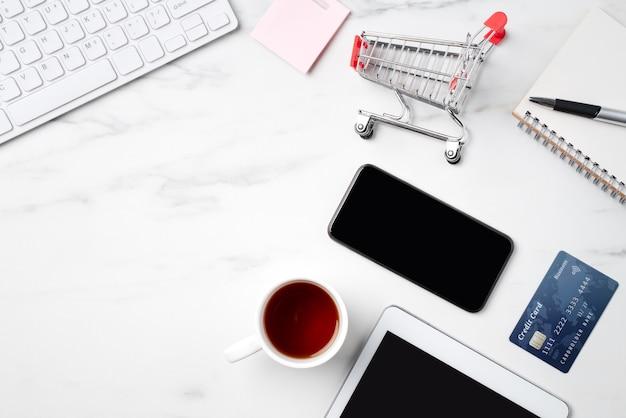 Vue de dessus du concept de magasinage en ligne avec carte de crédit et électronique isolé sur fond de table blanche en marbre de bureau.